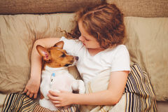 Girl and puppy under quilt with fever and temperature. Sick baby girl and puppy under quilt with fever and temperature Stock Photo