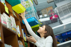 Girl purchasing bird cage in petshop Royalty Free Stock Photo