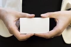 Girl with a pure business card. A young girl holds a clean card in her hand with your inscription. White isolated background Stock Image