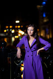 Girl in purple coat oudoor at night Stock Photo