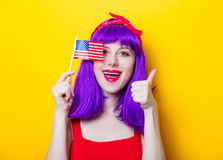 Girl with purple color hair holding USA flag. Portrait of young girl with purple color hair holding USA flag on yellow background royalty free stock image