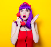 Girl with purple color hair and red handset Royalty Free Stock Image