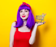 Girl with purple color hair and supermarket cart Stock Image