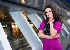 Girl in purple dress. Brunette girl in purple dress posing in the corridor Stock Photo
