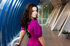 Girl in purple dress. Brunette girl in purple dress posing in the corridor Royalty Free Stock Photography
