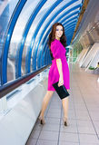 Girl in purple dress. Brunette girl in purple dress posing in the corridor Stock Photography