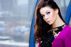 Girl in purple dress. Brunette girl in purple dress posing in the corridor Stock Photos