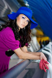 Girl in purple dress and blue hat. Brunette girl in purple dress posing in the corridor Stock Photos