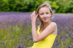 Girl in purple flowers outdoors in summer Stock Photo