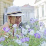 Girl in purple flowers. Girl sitting in flowers and smiling Royalty Free Stock Photography