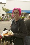Girl with purple hair eats food at annual Old Spanish Days Fiesta held every August in Santa Barbara, California stock photo