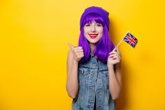 Girl with purple hair holding Great Britain flag. Portrait of young style hipster girl with purple hair and Great Britain flag in hand on yellow background Royalty Free Stock Images