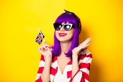 Girl with purple hair holding Great Britain flag. Young surprised girl with purple hair holding Great Britain flag on yellow background Stock Photo