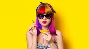 Girl with purple hair holding lemonade cocktail. Young girl with purple hair holding lemonade cocktail on yellow background royalty free stock photography