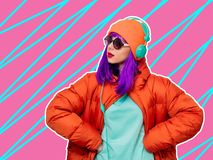Girl with purple hair in jacket with headphones stock image