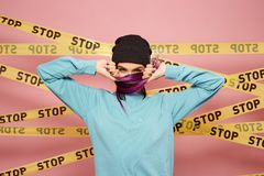 Girl with purple hair tips dressed in blue sweatshirt and black hat is grimacing on the background of pink wall with the royalty free stock photo