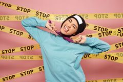 Girl with purple hair tips dressed in blue sweatshirt and black hat is grimacing on the background of pink wall with the royalty free stock images