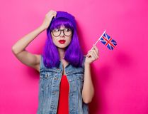 Girl with purple hair and United Kingdom flag. Portrait of young style hipster girl with purple hair and United Kingdom flag on pink background Stock Images