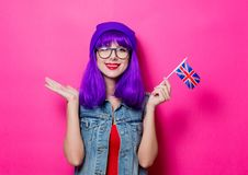 Girl with purple hair and United Kingdom flag. Portrait of young style hipster girl with purple hair and United Kingdom flag on pink background Stock Photography
