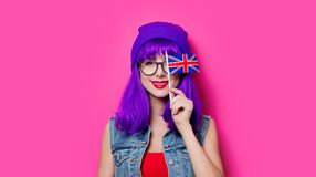 Girl with purple hair and United Kingdom flag. Portrait of young style hipster girl with purple hair and United Kingdom flag on pink background Royalty Free Stock Photos
