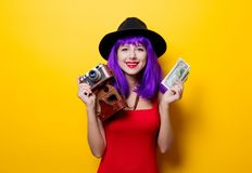 Girl with purple hairstyle with money and retro camera. Portrait of young style hipster girl with purple hairstyle with money and retro camera on yellow Stock Image