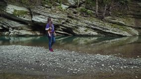 Girl in a purple jacket, jeans and sneakers wanders on a rocky island on a lake in the mountains. A girl in a purple jacket, jeans and sneakers wanders walks on stock video footage