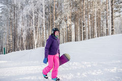 Girl in purple jacket and pink pants with snowboard in the hands Stock Photo