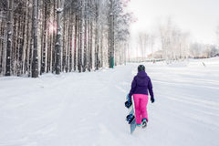 Girl in purple jacket and pink pants with snowboard in the hands Royalty Free Stock Image