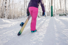 Girl in purple jacket and pink pants with snowboard in the hands Stock Photography