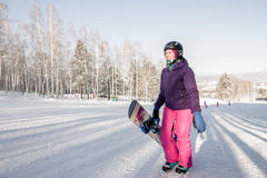 Girl in purple jacket and pink pants with snowboard in the hands Royalty Free Stock Photos