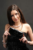 Girl with purse. Girl with a purse on a black background Stock Photography