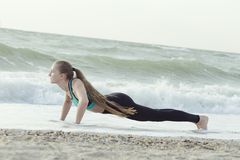 Girl push-ups on the beach, waves in the background.  stock images