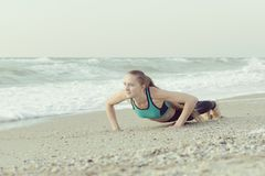 Girl push-ups on the beach, waves in the background.  royalty free stock image