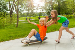 Girl pushes boy with arms apart on skateboard Stock Images