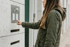The girl pushes the doorphone button or calls the intercom Royalty Free Stock Photography
