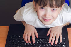 Girl pushes into laptop Royalty Free Stock Image