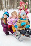 Girl pushes sled with two children, another one girl stands behind Stock Photo