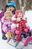 Girl pushes sledges with two younger children. In winter park stock photo