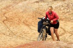 Girl pushing bicycle Stock Images