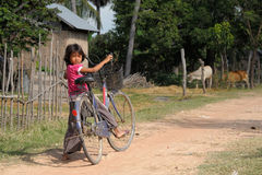 Girl pushing a bicycle Cambodian countryside Stock Photography