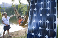 Girl pushing brother (5-9) in hammock by lake, solar panel in foreground, portrait of boy Stock Photography