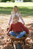 Girl (7-9) pushing brother (7-9) in wheelbarrow in garden, boy sitting on autumn leaves, smiling, portrait Royalty Free Stock Images
