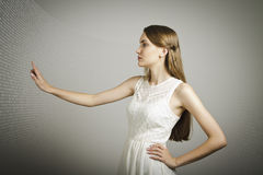 Girl pushing the button. Girl in white is pushing the virtual button. Internet concept Royalty Free Stock Photo