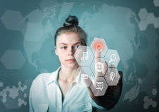 Girl pushing the button. Innovative technology concept. Young slim woman in white is pushing the virtual hexagonal button. Innovative technology concept stock photography