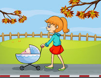 A girl pushing a stroller with a sleeping baby Stock Image