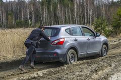 Girl pushing stuck car at swamp dirt road stock image