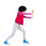 Girl pushing a wall Stock Images