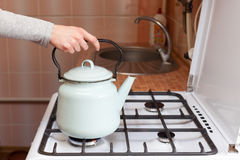 Girl put blue kettle on a kitchen gas stove. Girl put blue kettle on a kitchen gas stove royalty free stock images