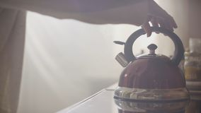 Girl put blue kettle on a kitchen gas stove. Stovetop whistling kettle in hand Stock Photo