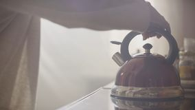 Girl put blue kettle on a kitchen gas stove. Stovetop whistling kettle in hand Royalty Free Stock Photography